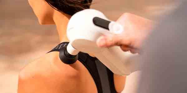 Usando la pistola de masaje en la espalda